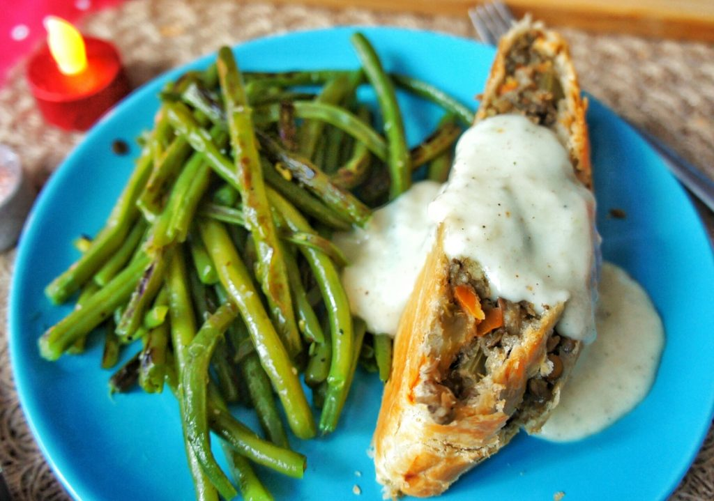Focus on the veggie wellington with a side of green beans.